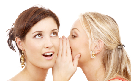 a girl telling another girl a secret