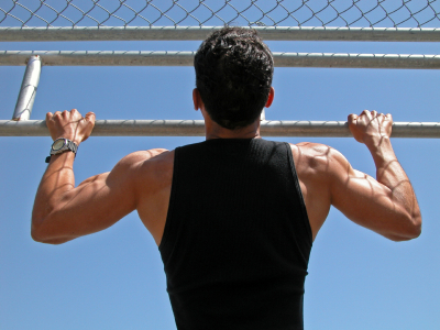 fit man performing chin ups outside